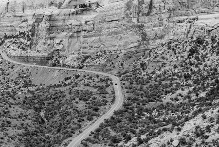 Cars driving the Rim Rock Drive, the road going through the Colorado National Monument, in the Fruita Canyon. The picture is in monochrome.