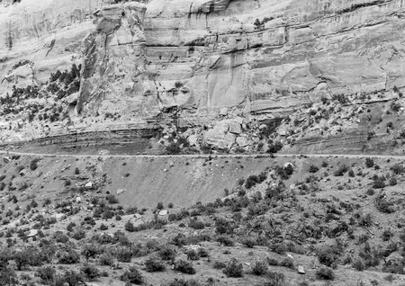 Part of the Rim Rock Drive, the road going through the Colorado National Monument, in front of a cliff. The picture is in monochrome. Stock Photo