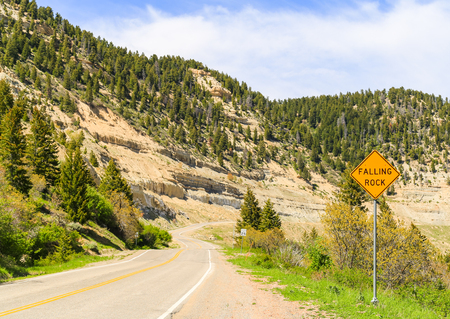 Warning sign on Colorado State Highway 139, called Douglas Pass Road, indicating the hazard of falling rocks, in the back a road sign showing the speed limit.