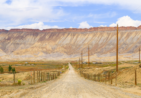 Motorcyclist on a gravel road leading towards the desert mountains Book Cliffs near Grand Junction in Colorado. Stock Photo