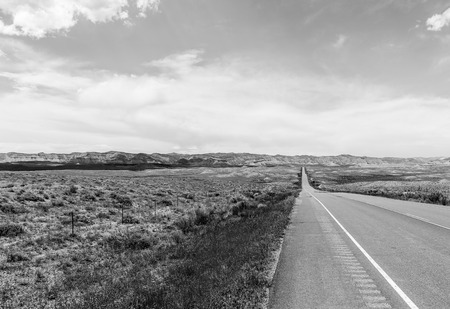 The Colorado State Highway 139 near Loma leading through the desert into the mountains. The picture is monochrome. Stock Photo