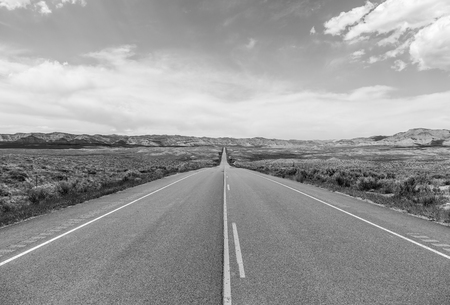 Colorado State Highway 139 near Loma leading through the desert into the mountains. The picture is monochrome. Stock Photo