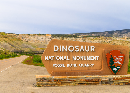 Jensen, USA - May 29, 2016: Entrance sign of the Dinosaur National Monument and the quarry that contains dinosaur fossils.