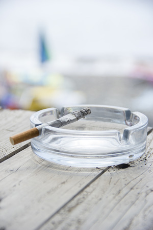 ashtray: Cigarette and ashtray on wooden table