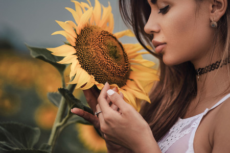 Young attractive woman holding a sunflower Stock Photo
