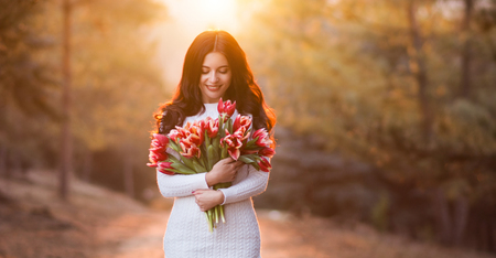 beautiful smiling woman with long hair holding in hands a bunch of spring flowers on the sunny background in the park