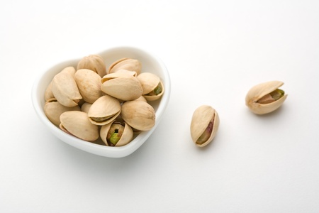 A plate and pistachio of white heart 版權商用圖片