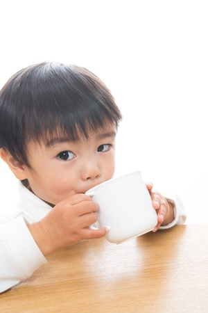 The child who drinks with a mug Stock Photo - 13153112