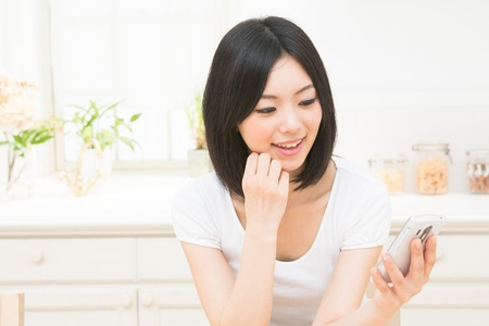 The woman who uses the smart phone in the kitchen Stock Photo