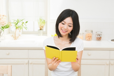 woman reading book: The woman who reads a book in the kitchen