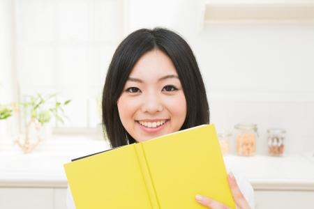 mujer leyendo libro: La mujer que lee un libro en la cocina Foto de archivo