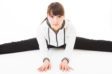 beine spreizen: Junge Frau, die Sport spielt