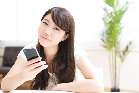The Young woman who uses the smartphone in a room Stock Photo - 17843979