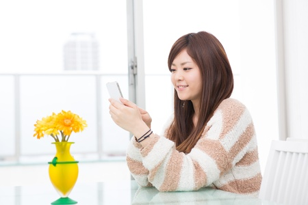 a young asian woman using smart phone in the dining room