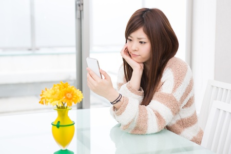 stay home work: a young asian woman using smart phone in the dining room