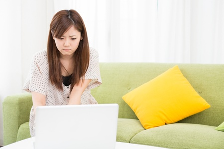 perplex: a young asian woman using laptop in the dining room