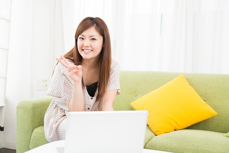 stay home work: a young asian woman using laptop in the dining room