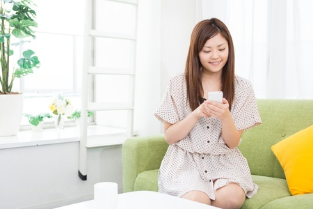 Beautiful young asian woman using smart phone photo