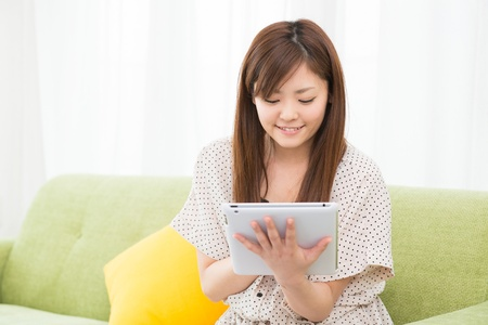 Beautiful young asian woman using tablet computer Stock Photo - 19628327