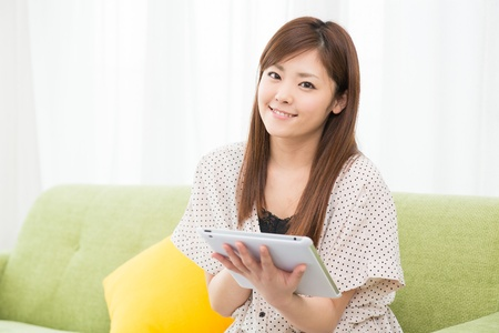 Beautiful young asian woman using tablet computer Stock Photo - 19628339