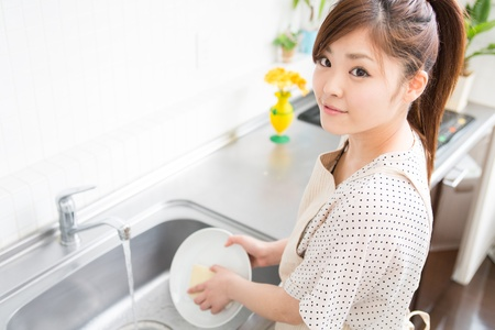 washup: young woman washed the dishes in a kitchen
