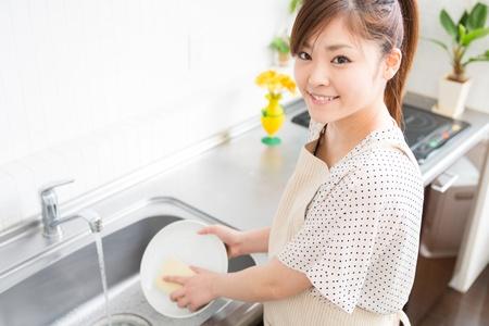 washup: giovane donna che lavava i piatti in una cucina