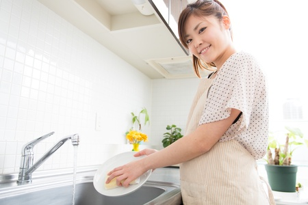 young woman washed the dishes in a kitchen photo