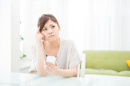 uneasiness: una mujer asi?tica joven que usa el tel?fono inteligente en el comedor