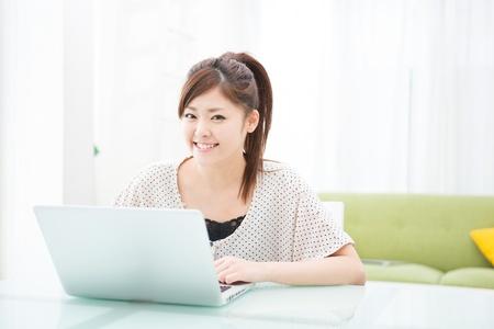 laptop asian: una mujer asi?tica joven utilizando equipo port?til en el comedor