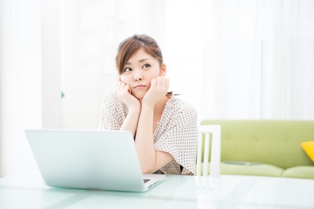 a young asian woman using laptop in the dining room