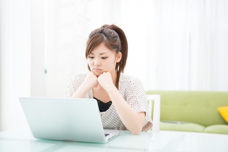 a young asian woman using laptop in the dining room photo