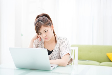 a young asian woman using laptop in the dining room Stock Photo - 19627685