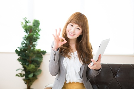 Beautiful young asian businesswoman using tablet Imagens