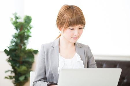 Beautiful young asian businesswoman using laptop Foto de archivo