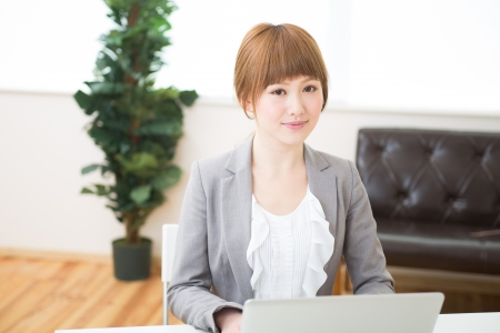 Beautiful young asian businesswoman using laptop photo