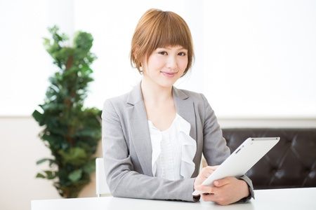 Beautiful young asian businesswoman using tablet computer photo