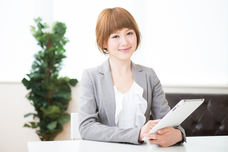 Beautiful young asian businesswoman using tablet photo