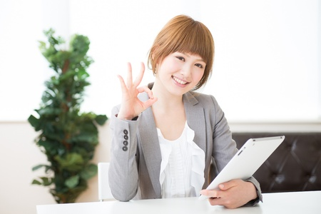 Beautiful young asian businesswoman using tablet computer