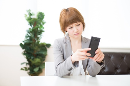 happening: Beautiful young asian businesswoman to see a smart phone