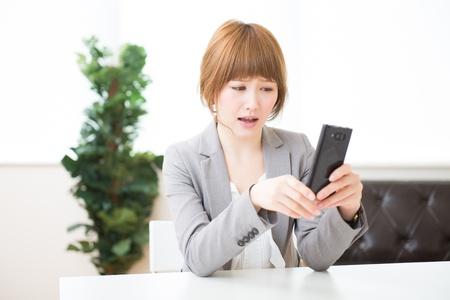 uneasiness: Hermosa joven empresaria de Asia para ver un tel�fono inteligente
