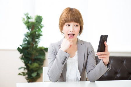 Beautiful young asian businesswoman to see a smart phone Stock Photo - 20072891