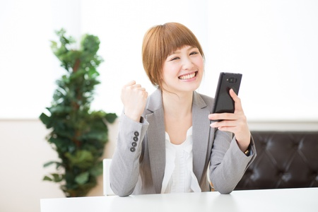 Beautiful young asian businesswoman to see a smart phone