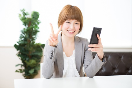 Beautiful young asian businesswoman to see a smart phone photo