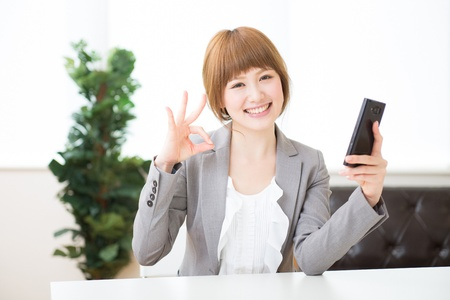 faithfulness: Beautiful young asian businesswoman to see a smart phone