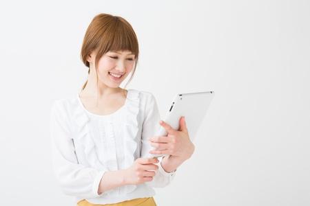 Beautiful young asian woman using tablet computer Фото со стока