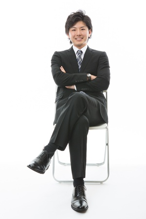 young businessman who sits down on a chair photo