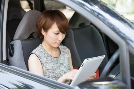 Beautiful young asian woman using tablet computer in a car Foto de archivo