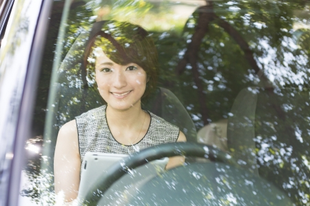 Beautiful young asian woman using tablet computer in a car photo