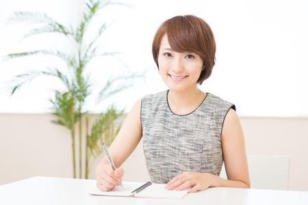 ノートを入力している美しい若いアジア女性