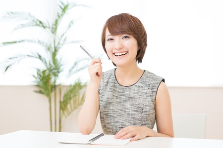 Beautiful young asian woman who fills out a notebook photo